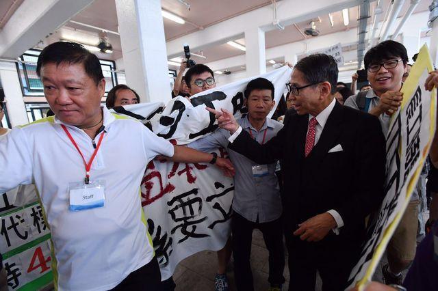 梁智鴻在保安人員協助下進入會場。