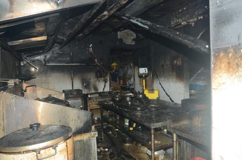 消防在嚴重焚毀的廚房調查。楊偉亨攝