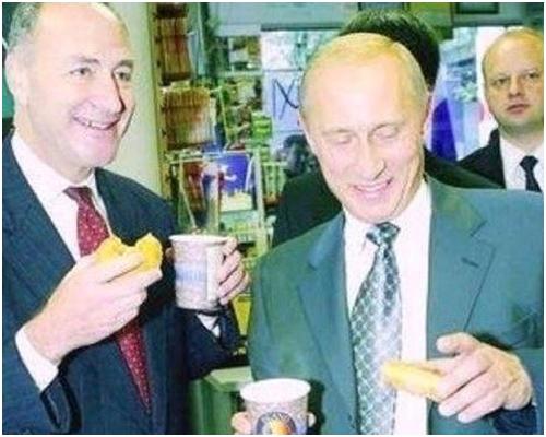 舒默(左)和普京並肩站著,笑容滿面,拿著咖啡和冬甩。網圖