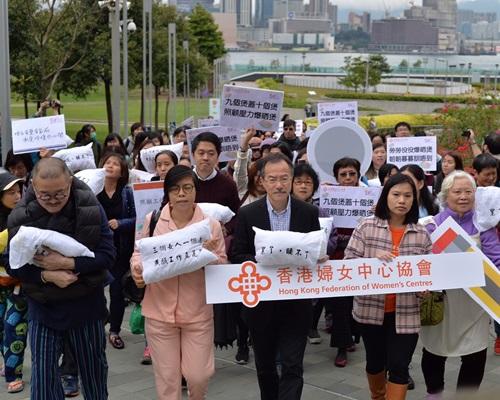 近百人手持寫上標語的枕頭遊行。郭顯熙攝