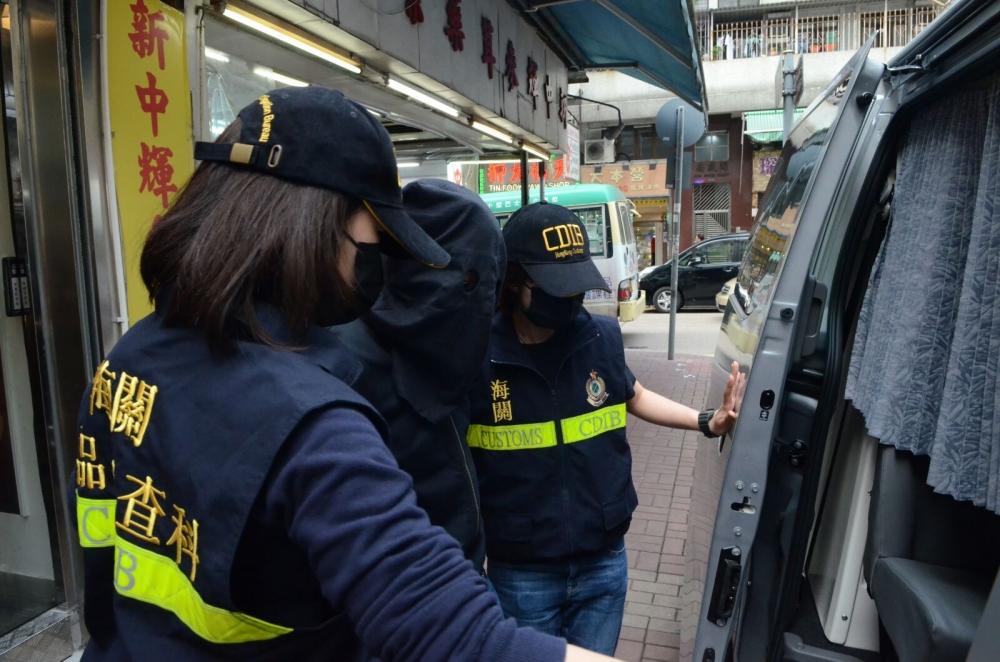 海關人員將疑犯押返單位搜證。李子平攝
