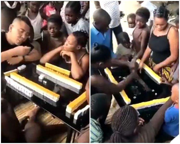 一名內地男子向圍觀的多名非洲小朋友示範如何打麻將。片段截圖