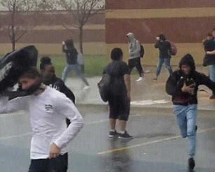 片段中一名男學生雨中動也不動地站着,面向着校舍。網圖