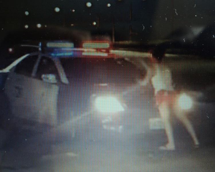 醉酒女子以身阻擋警車離去。