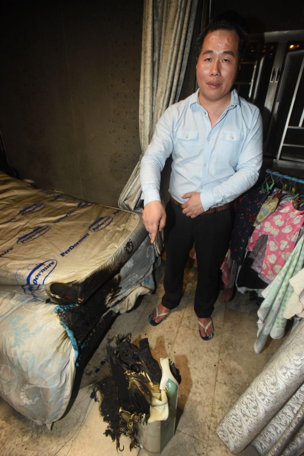 林先生展示焚毀的床褥及抽濕機。徐裕民攝