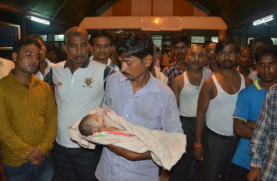 父親手抱死去嬰兒。AP圖片
