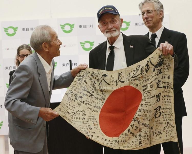 美國海軍陸戰隊士兵交還日本國旗予戰死的日軍士兵家屬。網圖