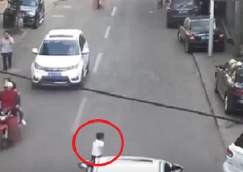 衝出馬路的男童被汽車撞倒並捲入車底。 網上圖片