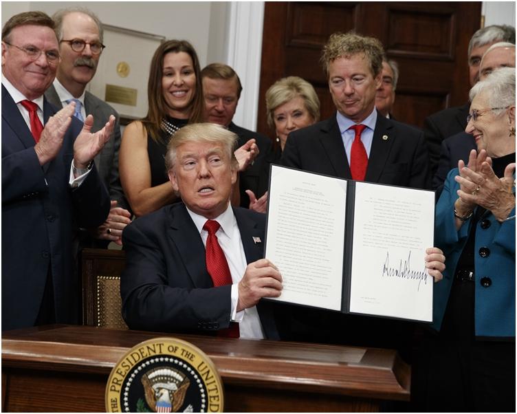 特朗普經提醒後,才轉身走到辦公桌,坐下簽署。AP