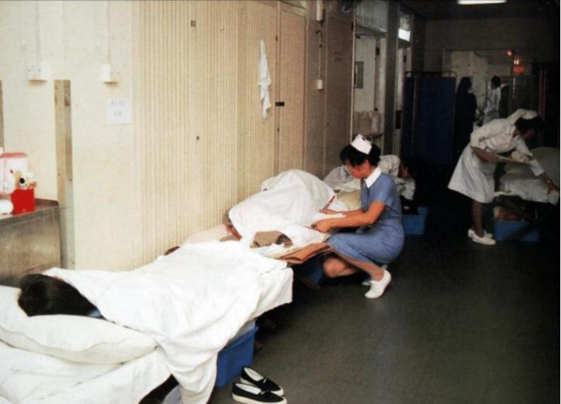 80年代,伊院走廊滿佈帆布床,情況擠迫,護士要蹲下來照顧病人。