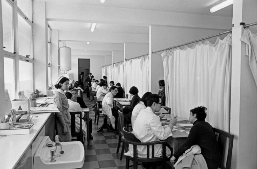 70代醫生診症的情況。當時尚未有保障病人私隱的概念,不同醫生在同一空間為病人診症。政府新聞處提供