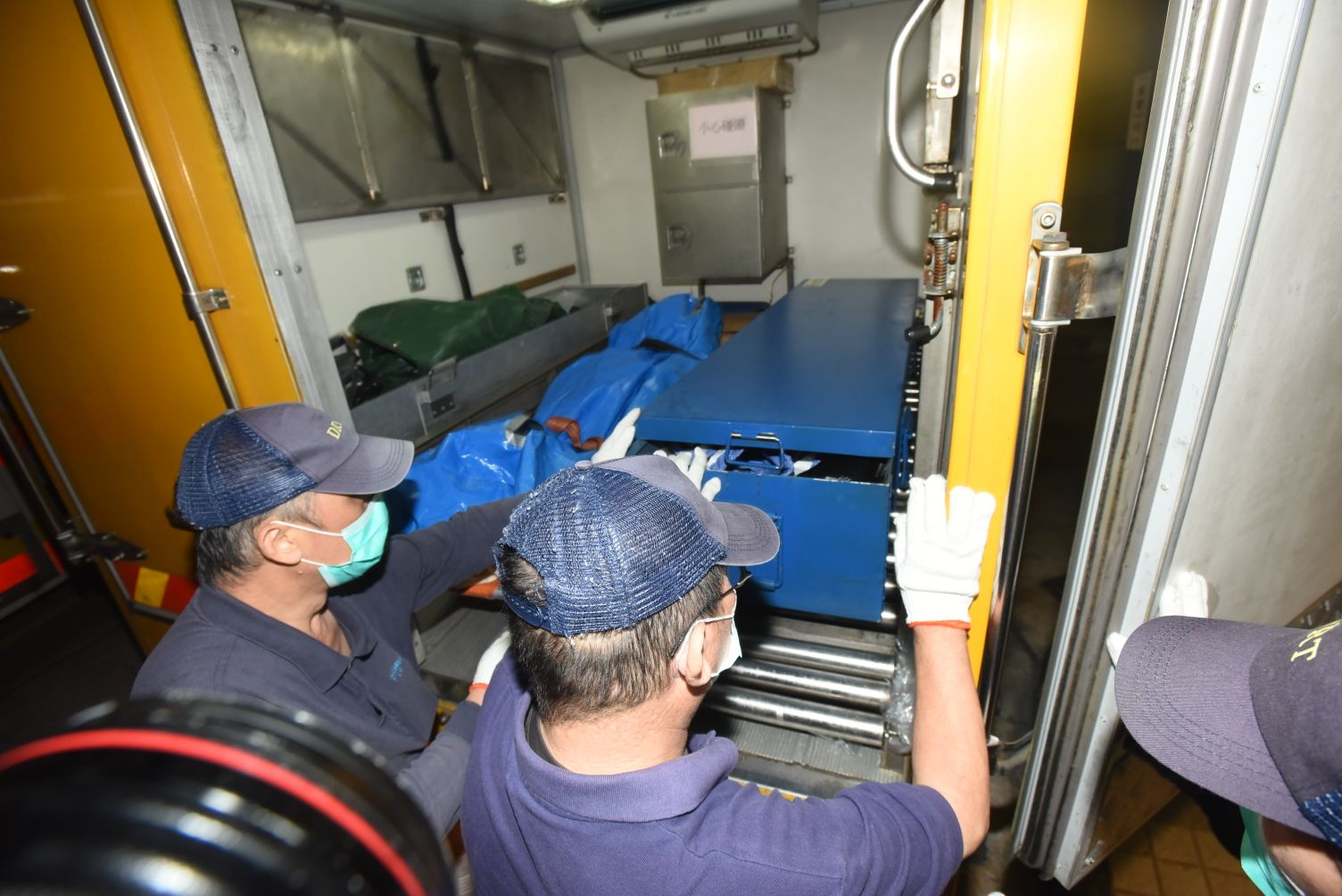 兩人的遺體其後由仵工舁送殮房,藍袋內為男死者(左)、藍鐵箱內則為女死者。徐裕民攝