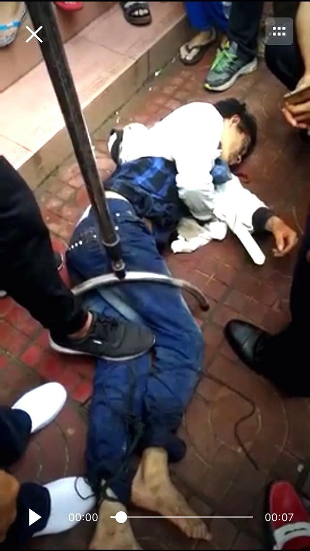 持刀男被警員用鋼叉制服,按倒在地。
