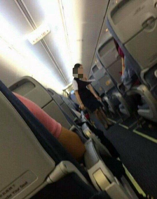 照片中空姐左肩的衣服被撕爛,仍在堅持工作
