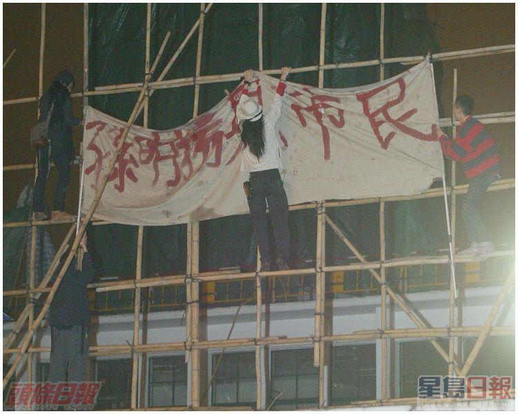 示威者攀上地盤棚架,掛上反對拆卸的橫額。資料圖片