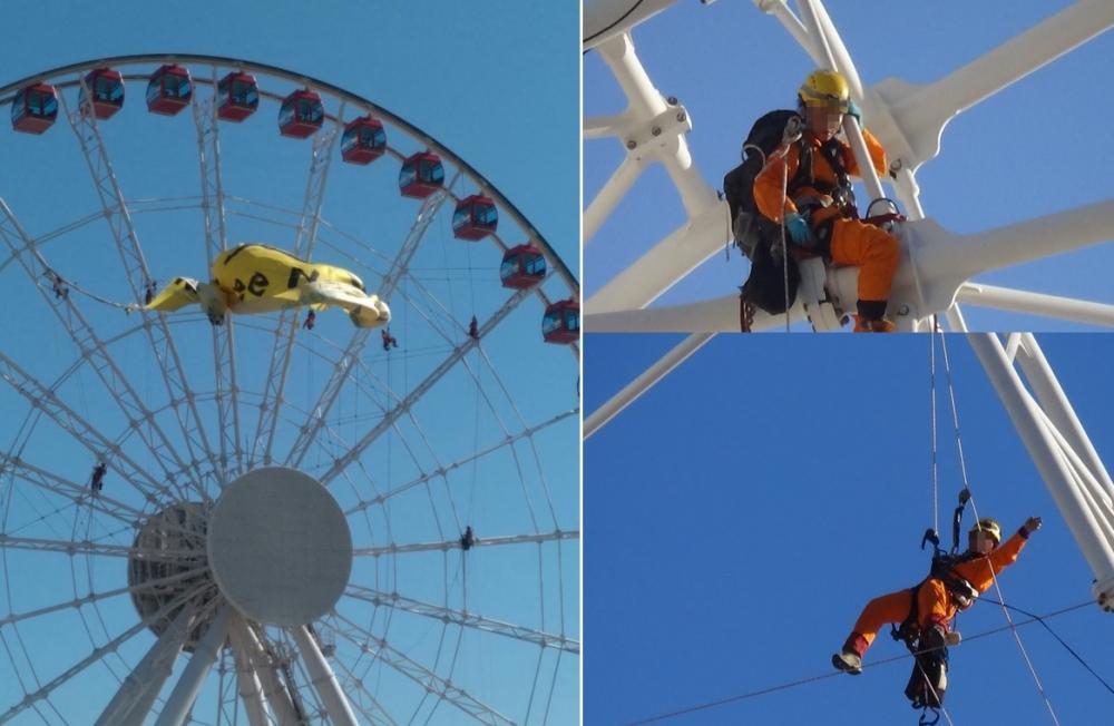 12名成員爬上摩天輪示威並企圖掛上橫額。