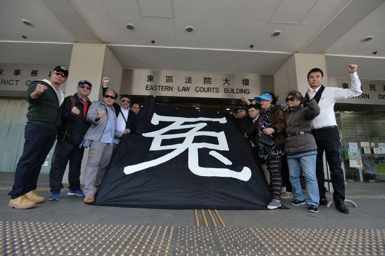 「珍惜群組」成員於庭外拉起寫有「冤」字的黑布。
