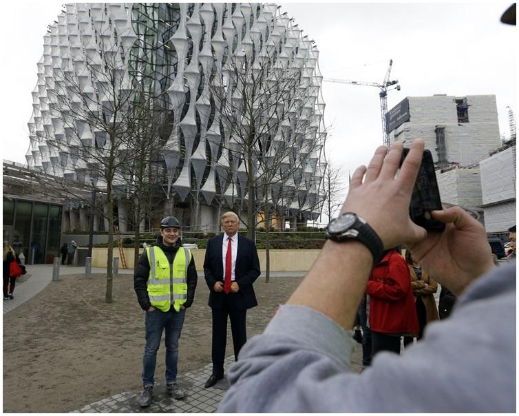 連使館人員都加入工人行列在蠟像旁觀看並自拍。AP