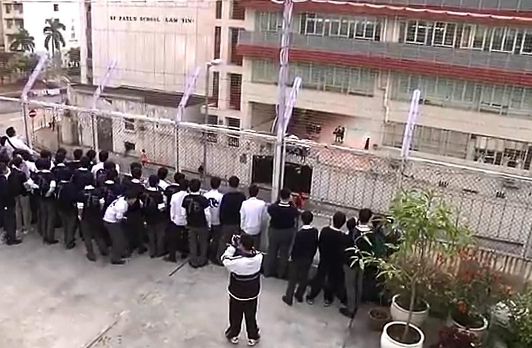 聖言中學一班男校生隔著圍欄,向對面的女校同學獻唱《對面的女孩看過來》。影片截圖