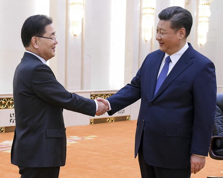 習近平(右)與鄭義溶(左)握手。AP