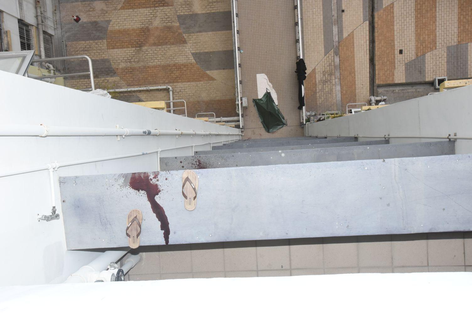 12樓走廊有一對拖鞋,而石壆和外牆留有血迹。徐裕民攝
