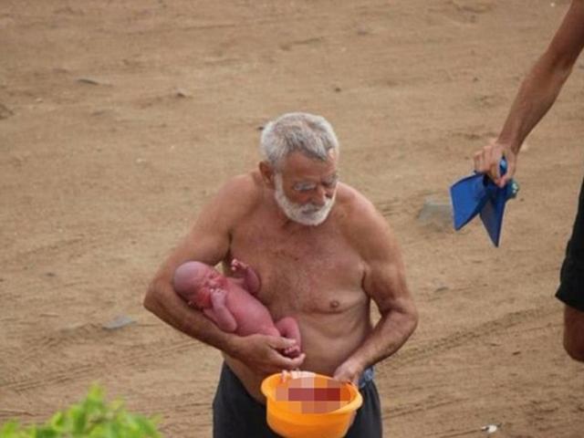 醫生抱著未剪臍帶的嬰兒上岸。 網圖