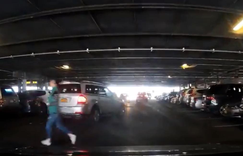 司機將車輛駛入車位期間,一名華裔女子在其車前跑過。影片截圖
