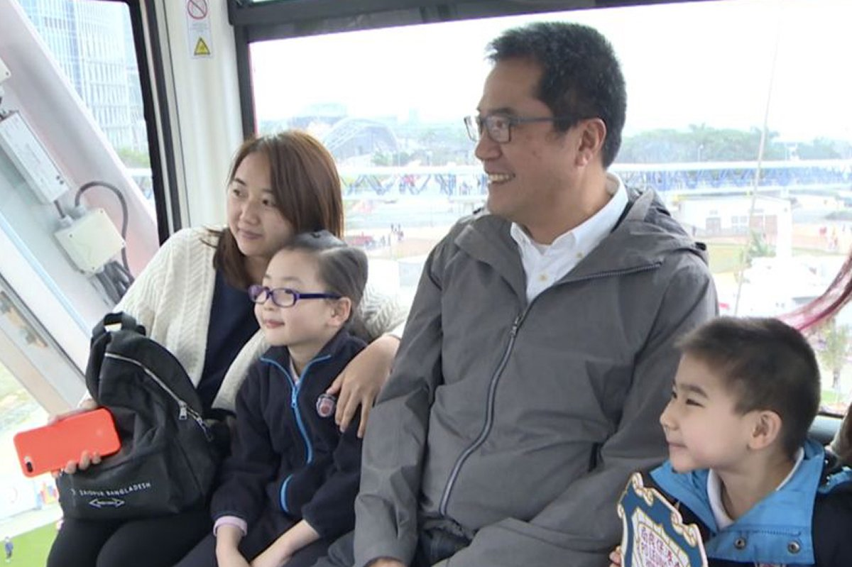 黃偉綸(右二)與學童和家長在摩天輪車廂合照留念。