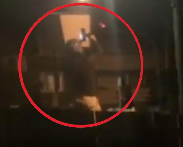 一名帶著頭盔的男子順著長桿爬到了被毀的攝影鏡旁邊。網圖