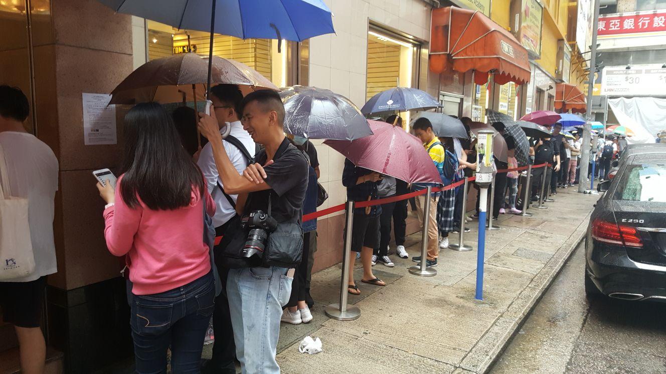 大批市民冒雨排隊。
