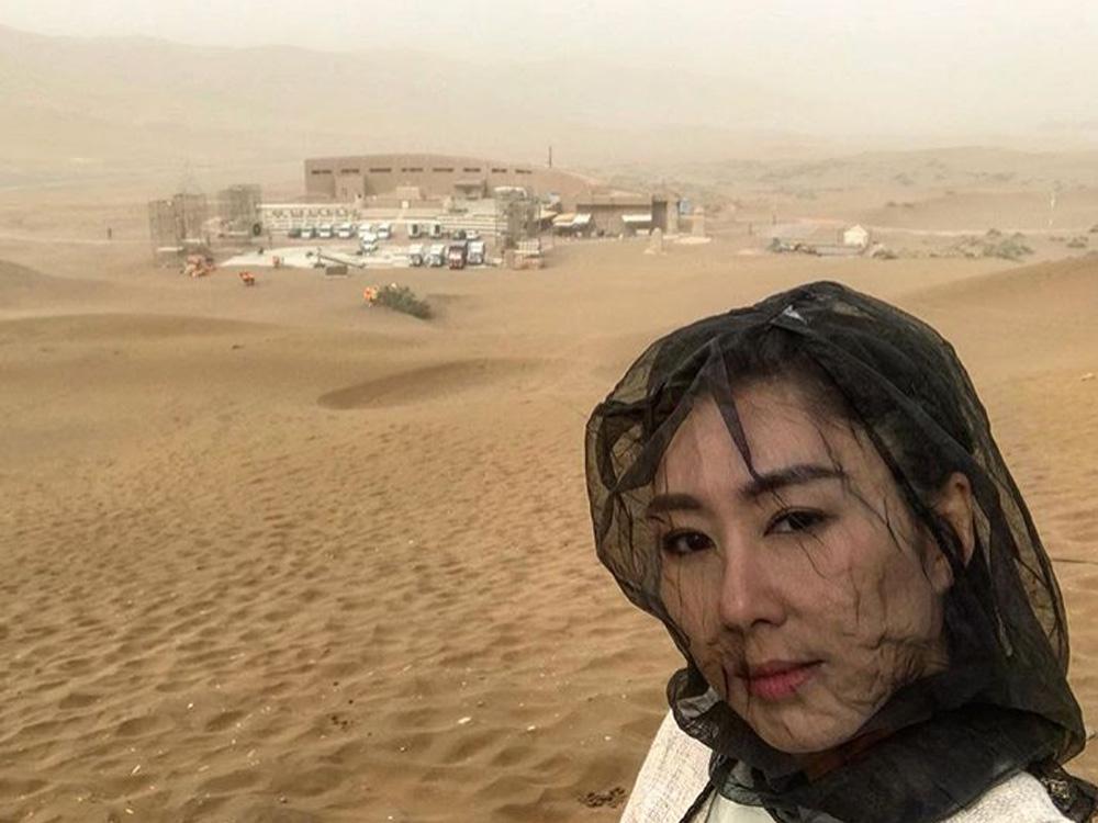 因當地好大沙塵,所以定欣要用黑紗包頭。
