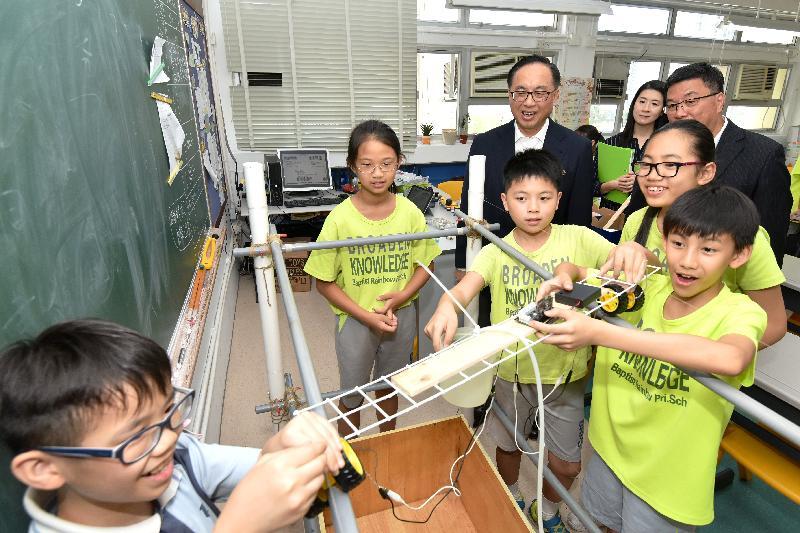 楊偉雄(後排左)在浸信會天虹小學觀看學生參與自主學習活動。政府新聞處圖片