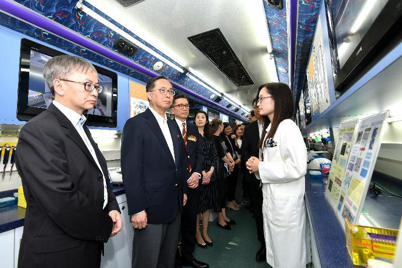 楊偉雄(左二)在黃大仙祠參觀嗇色園生物科技流動實驗室,了解其推廣生物科技教育的工作。政府新聞處圖片