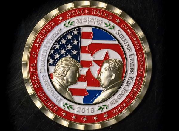 紀念幣上印有特朗普與北韓領導人金正恩面對面的金色浮雕,背景是拼接的兩國國旗。