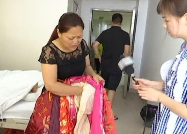 楊女士展示其他家人為婆婆穿上的壽衣。(網圖)