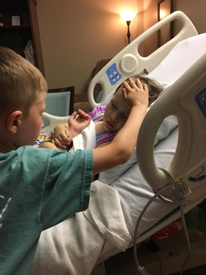 6歲哥哥Jackson站在病床邊,注視着與病魔搏鬥的妹妹,右手輕撫上她的前額,畫面令人動容。