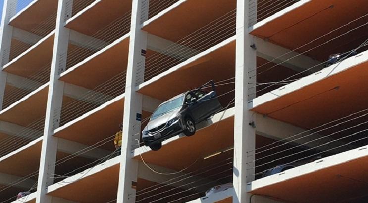 美國一名六旬婦在停車場駕駛期間,錯將油門當成煞車,結果私家車加速,並衝出安全圍欄,懸吊在4樓半空。