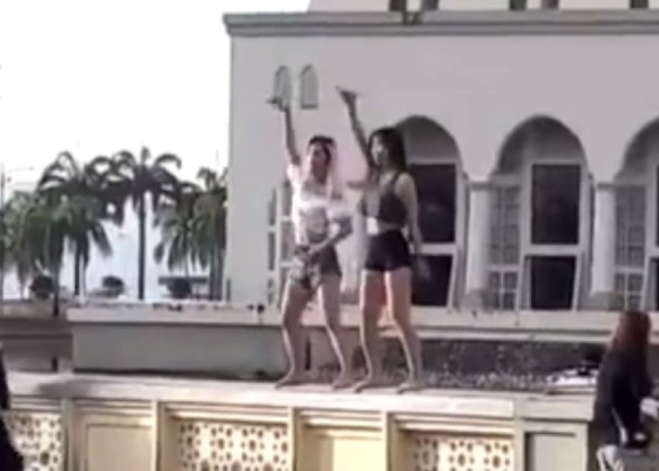 兩名中國女遊客在沙巴的清真寺前圍牆上熱舞,惹來各方猛烈評擊。(網圖)