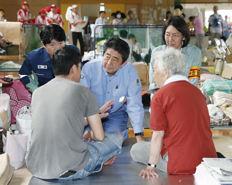 安倍晉三(中)到岡山縣慰問受難災民。AP
