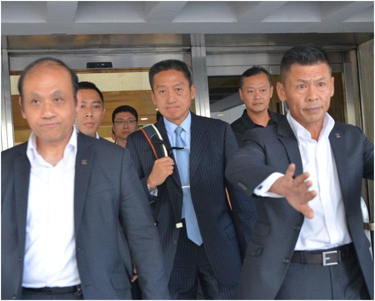 朱經緯在數人護送下離開法院。