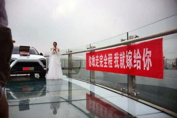 穿好婚紗的小靜帶着名車與百萬嫁妝,在高空玻璃走廊上向男友小宇求婚。(網圖)