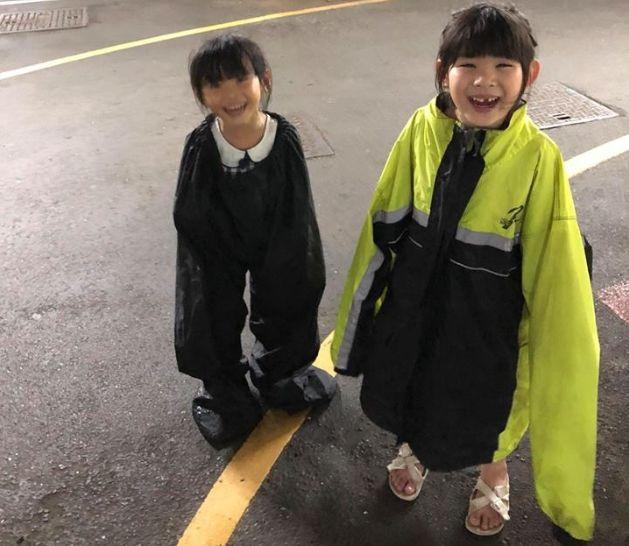 父親巧妙地將雨褲和雨衣,讓兩名女兒分開穿上。網圖