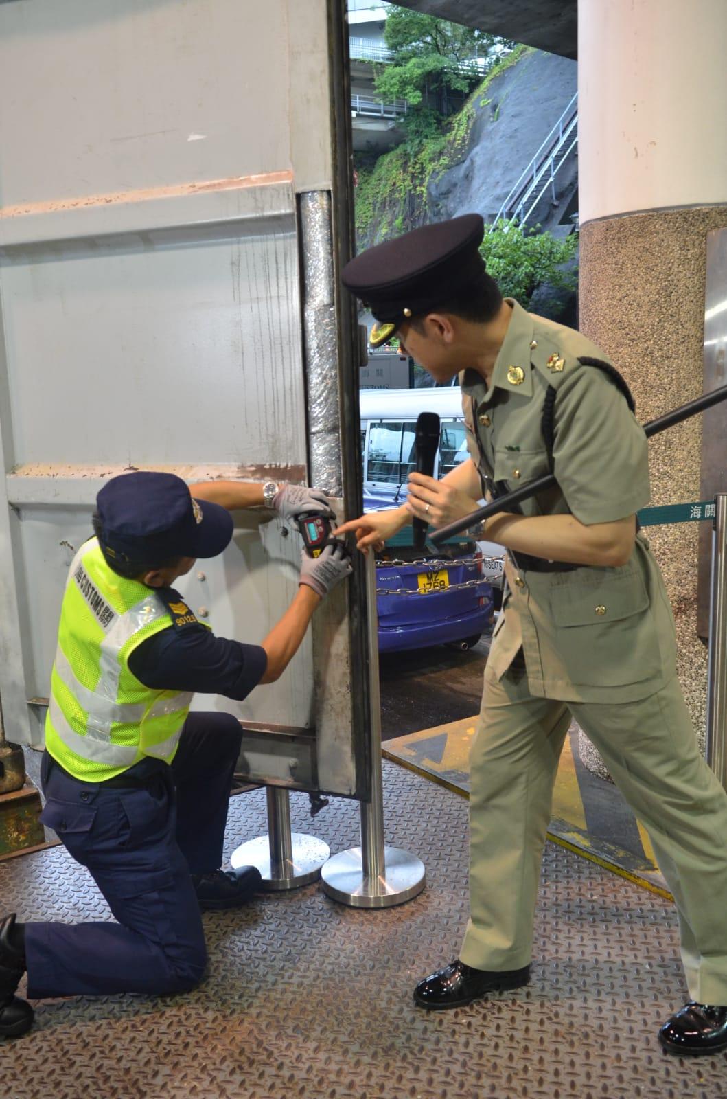 海關關員示範用密度 儀,測量有關貨櫃門的密度。