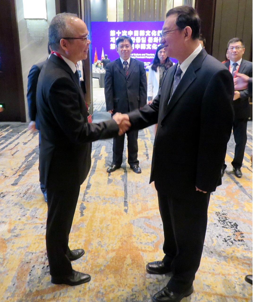 劉江華(左)與雒樹剛握手。政府新聞處圖片