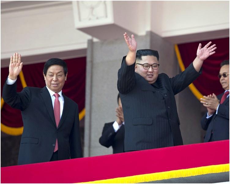 栗战书站在金正恩旁边高举握着的手向台下的民众致意。