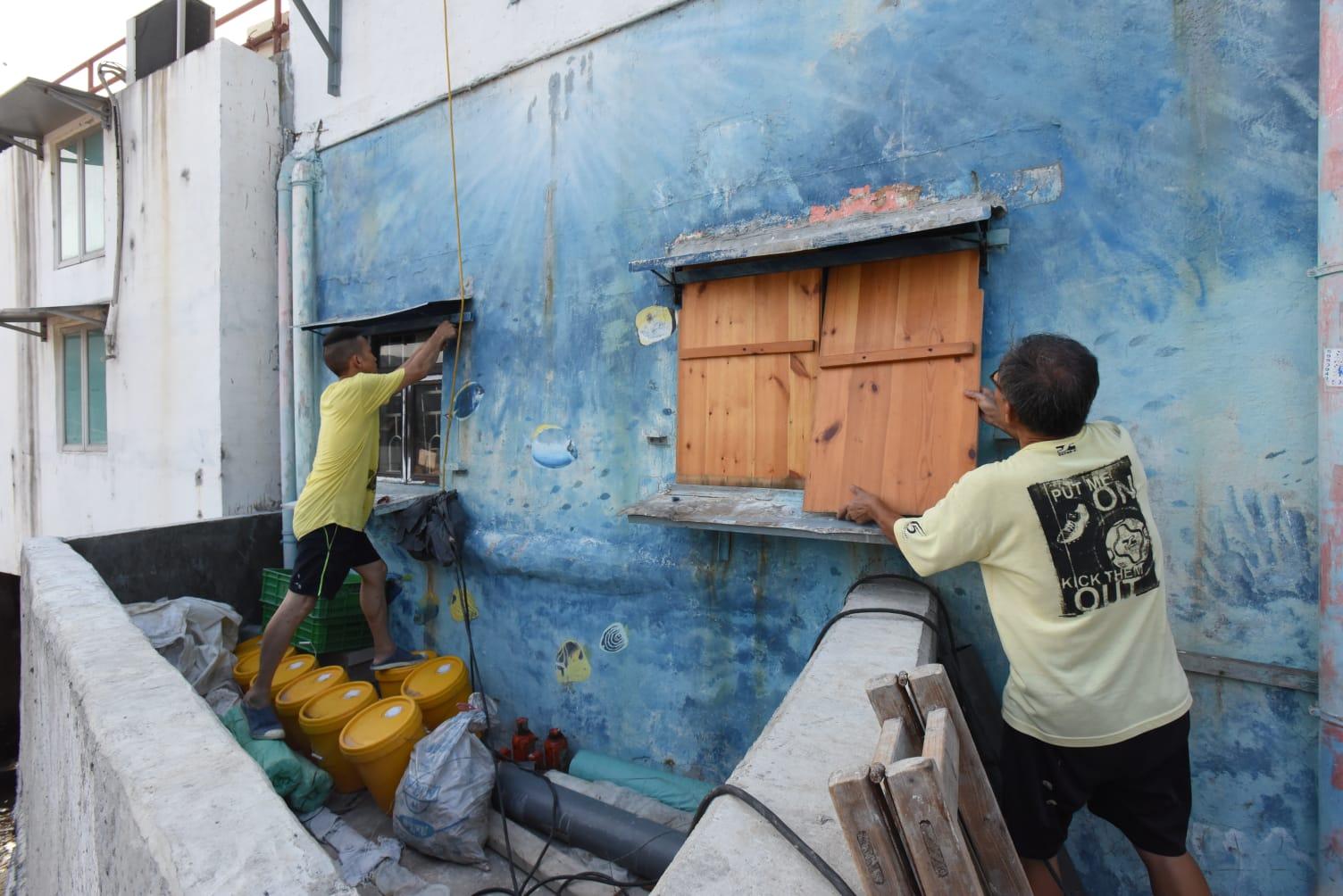 馬環村村民周先生在窗戶封上木板,預防「山竹」吹襲。徐裕民攝