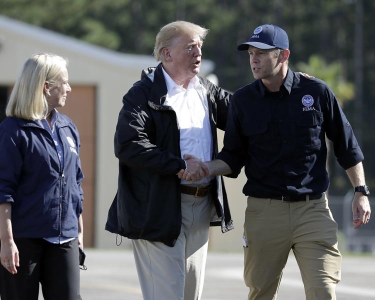 特朗普(中)與尼爾森(右)握手。AP