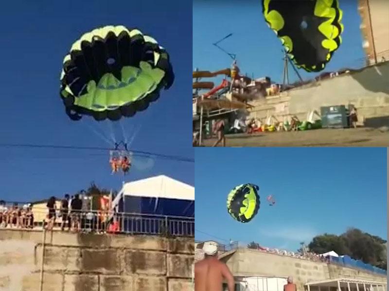 俄羅斯某渡假村一對情侶在海灘玩滑翔傘時,卻不慎碰到高壓電纜。(網圖)