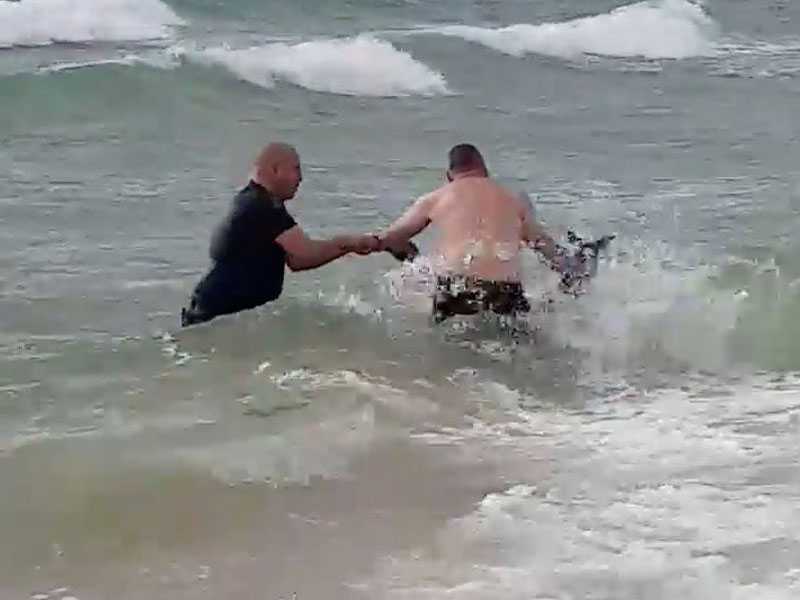 兩警員一人抓尾,一人搬頭,將袋鼠救回上岸。(網圖)