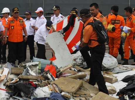 工作人员在雅加达的一个码头货仓检查飞机残骸和寻获的乘客私人物品。